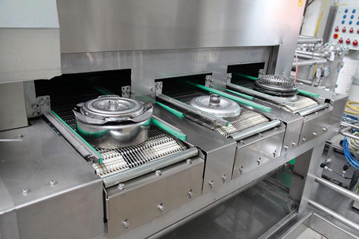 Unterschiedliche Wandlerkomponenten fahren auf getrennten Förderbändern in BvL-Reinigungsanlage ein.